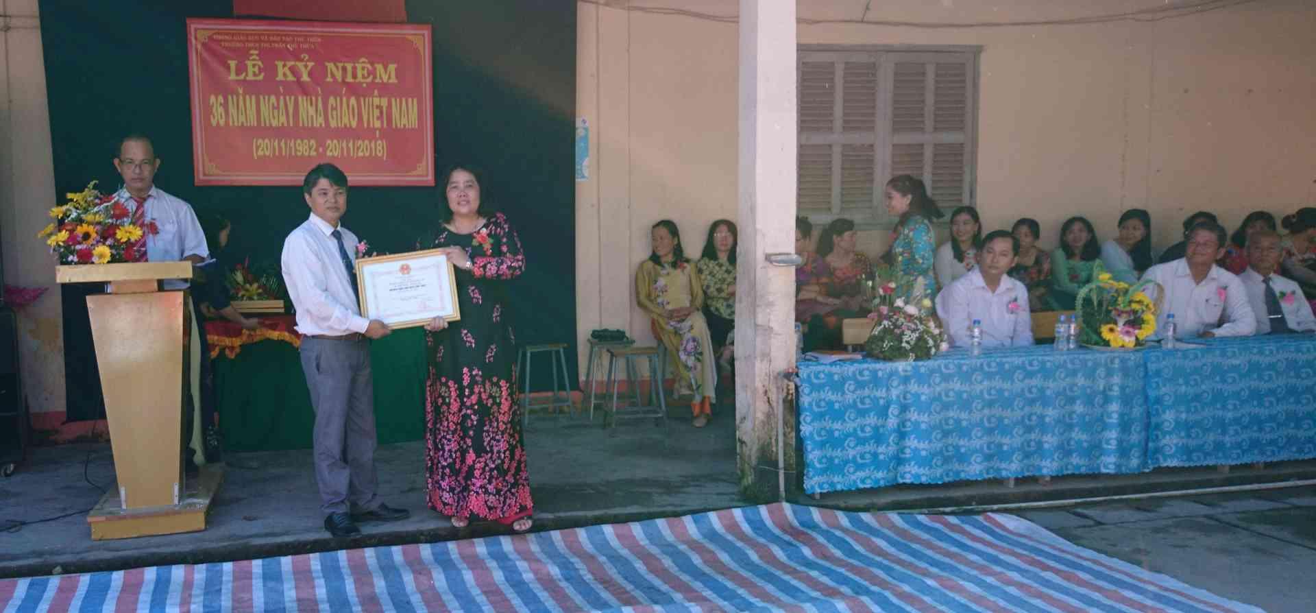 Trưởng Phòng GD&ĐT huyện ( bìa trái) trao bằng khen của UBND Tỉnh cho tập thể trường THCS Thị trấn Thủ Thừa